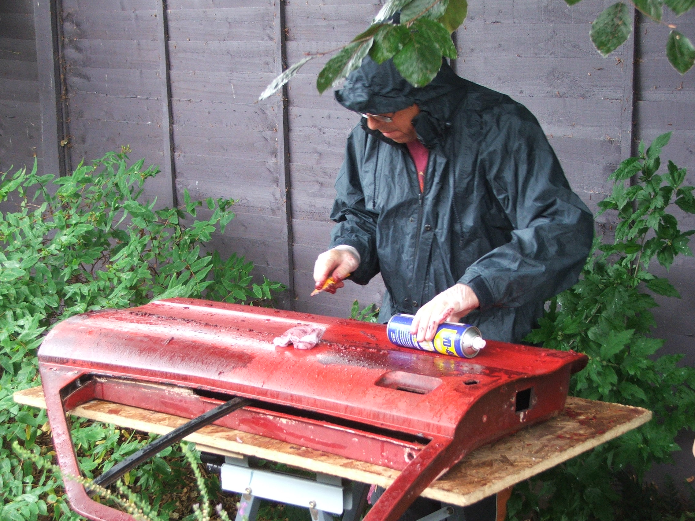Geoff Ward works through the rain shower stripping a door from Quantum Coupé 003